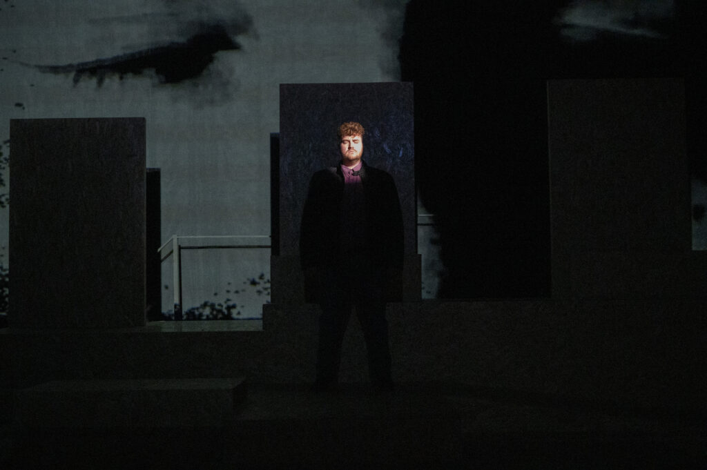 A young white man stands on stage, his face picked out by a thing shaft of light. Behind him is a video projection of a close up of his eyes.