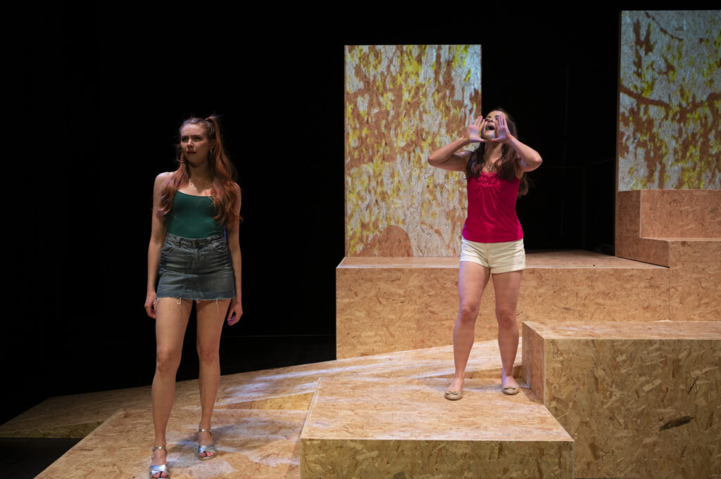 Two young women stand on stage. On the right hand side, the girl is screaming with her hands to her mouth. Behind her on the theatre set is a projection of leaves in summer.