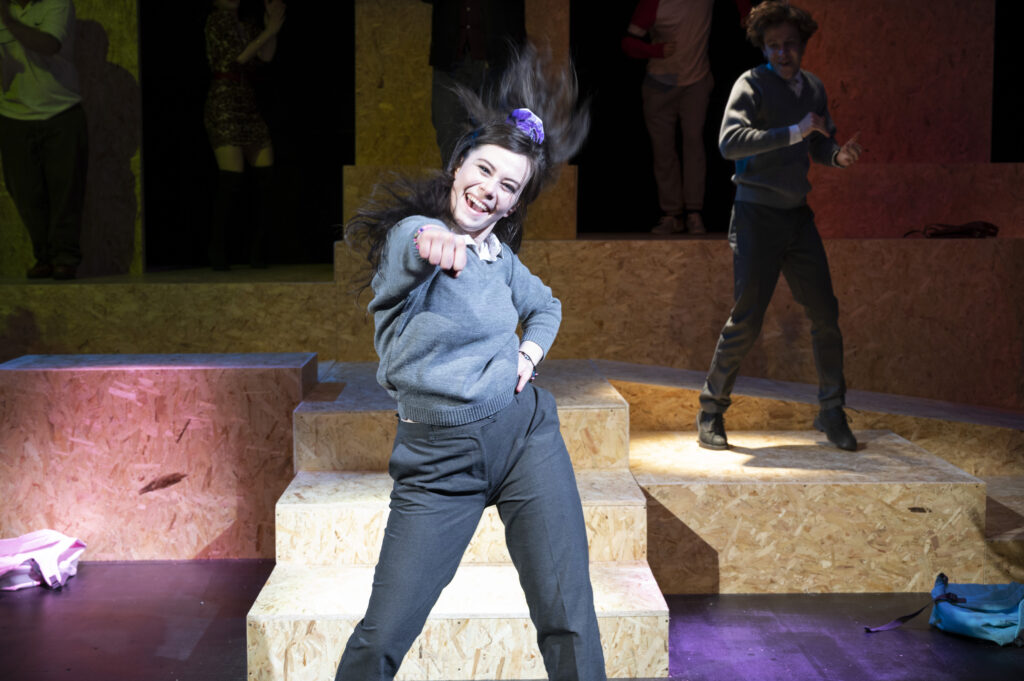 An actor playing a teenage girl in school uniform dances towards the camera her fist out. Behind her other performers dance.