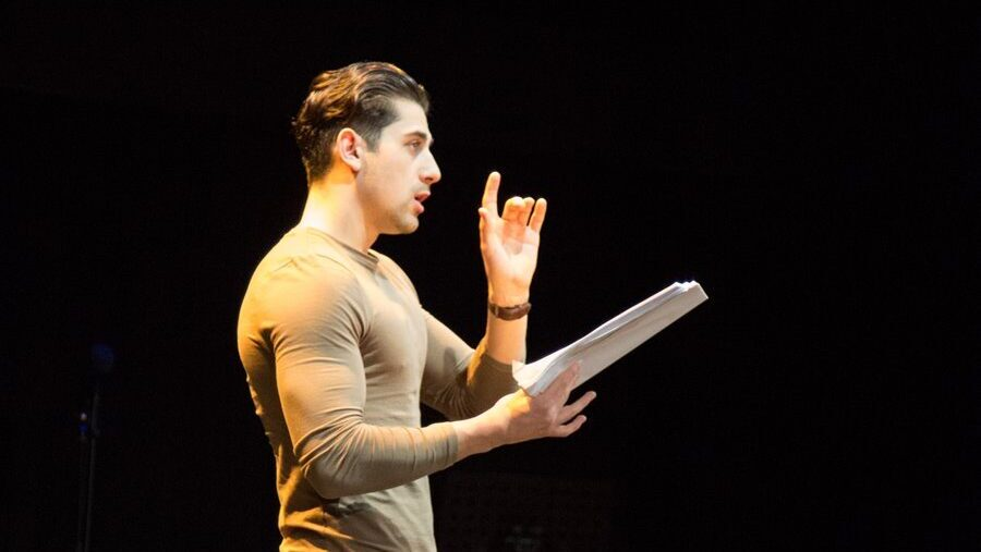 A man performs with a script in his hand. He holds his left hand up as he speaks.
